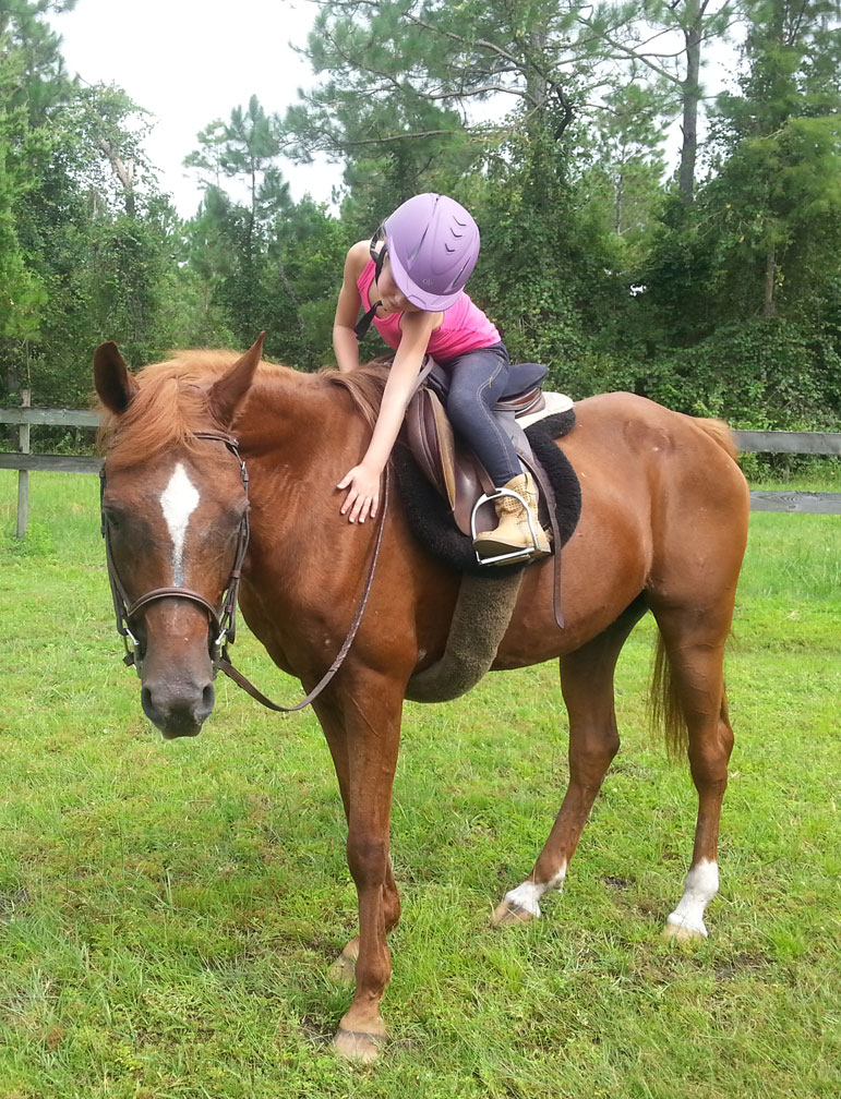 Girl riding and petting Mystique horse at Throwing Copper Farm Ormond Beach FL 32174